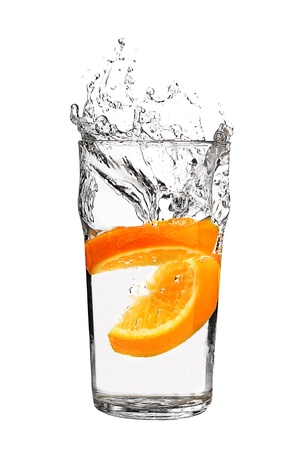 fruit drop: orange splashing into glass of water on white background  Stock Photo