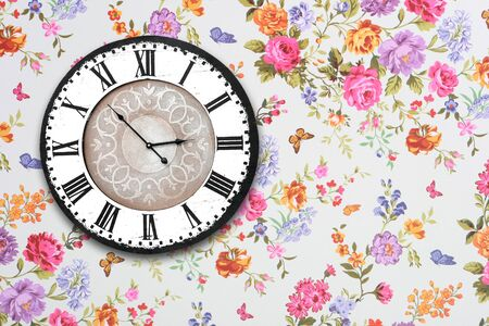 wooden retro clock on floral wallpaper photo