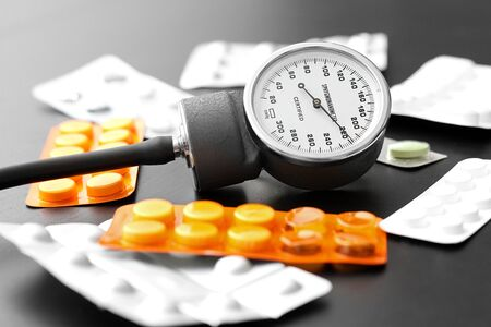 blood pressure meter and pills on the table photo