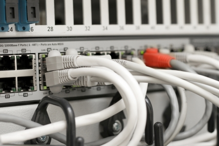 ethernet cable: network hub and cables connected to servers in a datacenter Stock Photo