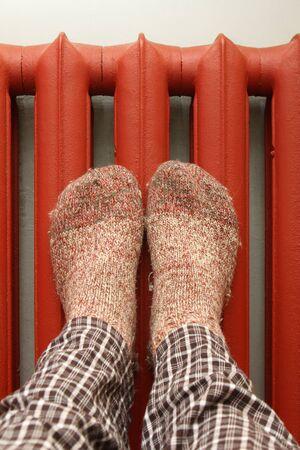 hosiery: feet with wool socks warming on the radiator Stock Photo