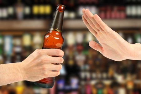 hand reject a bottle of beer in the bar Stock Photo