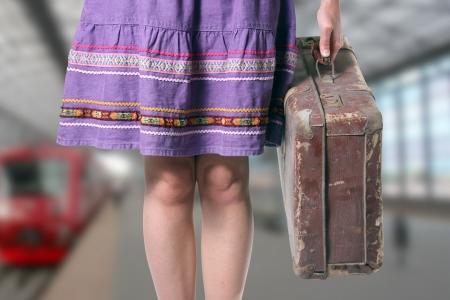 mujer hippie: chica con una maleta retro en la estación de tren
