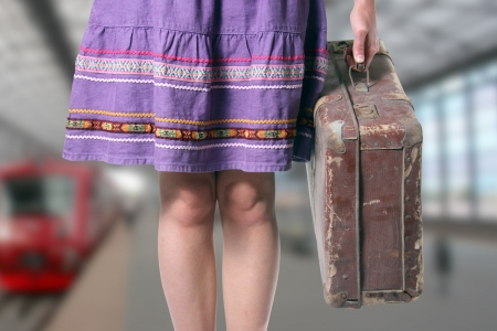 girl with a retro suitcase at the train station