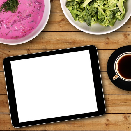 digital tablet with white blank screen on dinner table photo