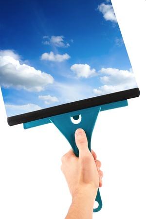 cleaners: hand met raam schoonmaken tool en de blauwe hemel
