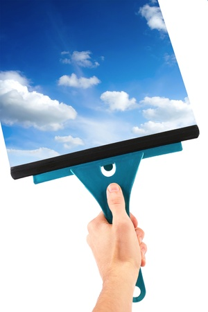 clean window: hand with window cleaning tool and blue sky Stock Photo