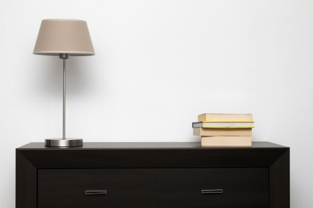 lamp house: brown commode with lamp and books in bright minimalism interior Stock Photo