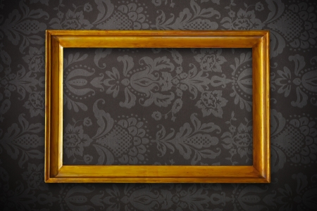 golden vintage empty frame on dark floral wallpaper photo