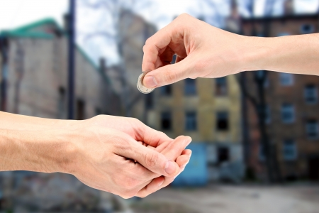 gives: Hand gives coin to beggar on the street Stock Photo