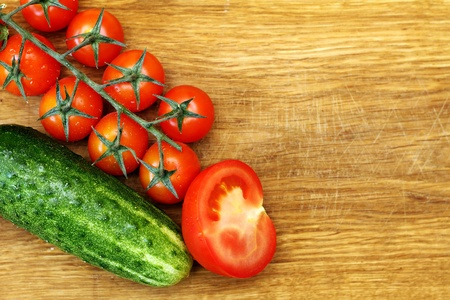 cutting vegetables: tomatos and cucumber on wooden cutting board Stock Photo