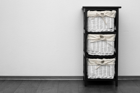 brown shelf with wicker baskets at white wall photo