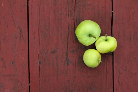 three green apples on red old wooden table photo