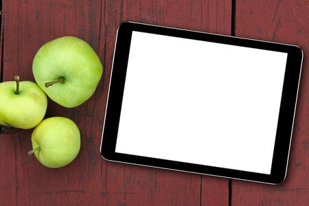 empty tablet and apples on the red wooden table Stock Photo - 21171364