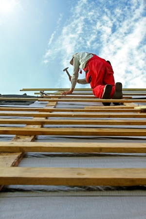 roof beam: construction worker with a hammer on the roof