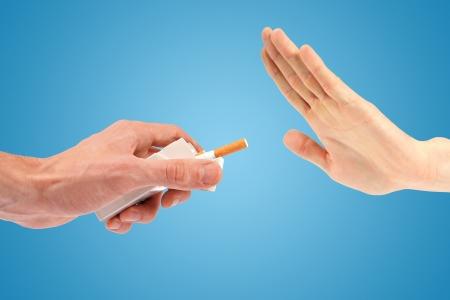 fumando: entregar rechazar una oferta de cigarrillos. aislado en azul Foto de archivo