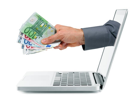 coming out: internet earnings concept - hand with money coming out from laptop screen Stock Photo