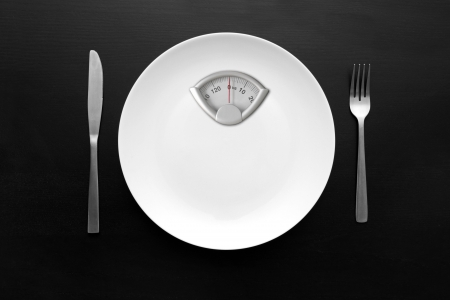 anorexia: dieting concept - white plate with weight scale
