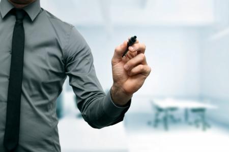 オフィスでの手で黒のマーカーで実業家