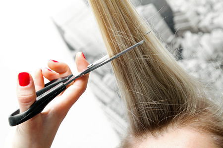 woman cutting long hair with scissors photo