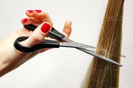 hand with scissors cutting long hair photo