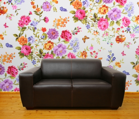 sitter: interior with brown leather couch against colorful floral wall