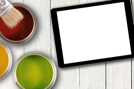 tablet with blank screen and colorful paint cans photo