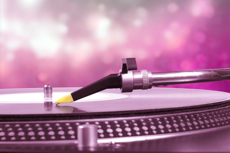 electronic music: dj turntable with pink bokeh background