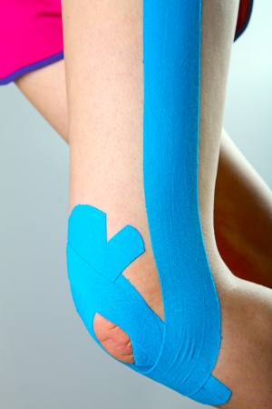 physiotherapy - knee with blue kinesio tape photo