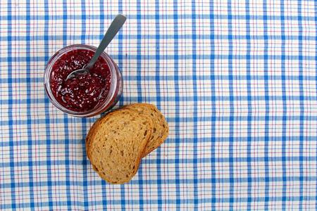 jar with raspberry jam and sliced bread on blue tablecloth photo