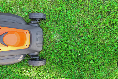 mowing lawn: lawnmower on green grass