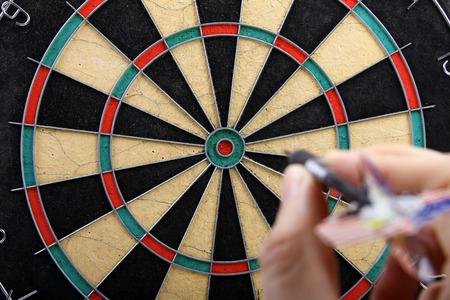dartboard: hand throwing dart to dartboard