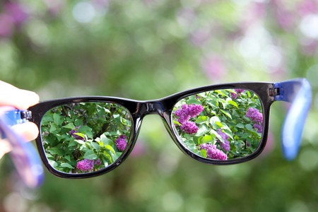 blurred vision: eyeglasses in the hand over blurred background