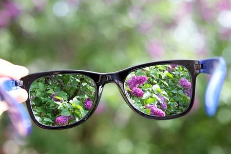lentes de contacto: gafas en la mano sobre fondo borroso