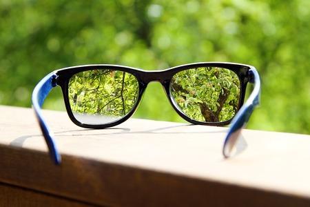 lentes de contacto: gafas en la mano sobre fondo borrosa árbol