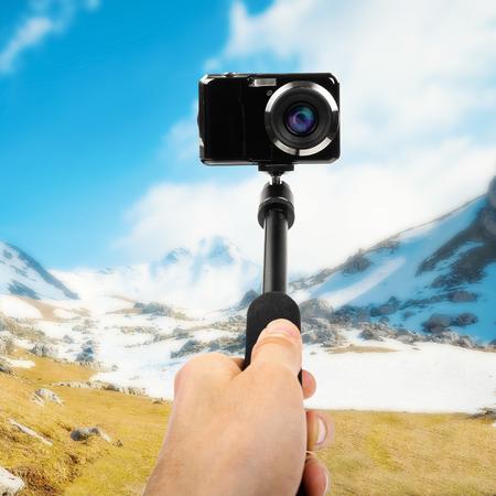 taking selfie - hand hold monopod with photo camera Stockfoto