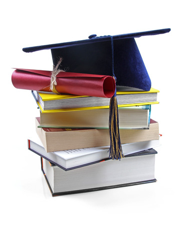 graduation hat and diploma on stack of books photo