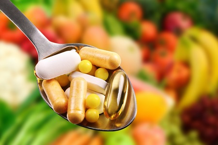 spoon with dietary supplements on fruits background Stockfoto