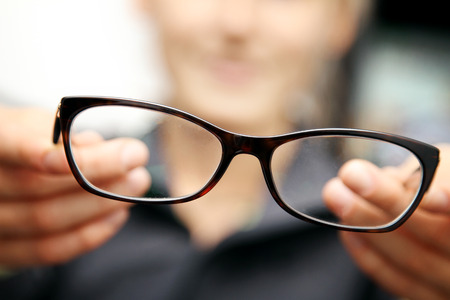 woman hands hold eyeglasses in front of her