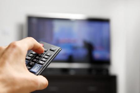 asimiento de la mano del mando a distancia delante de la TV