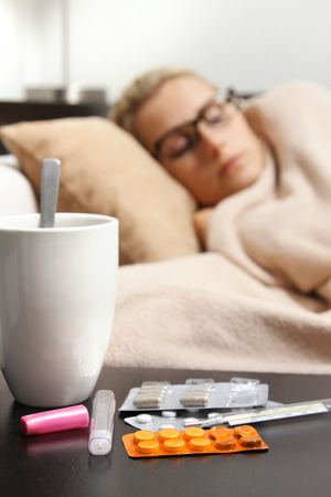 sick woman sleeping in bed, focus on pills photo