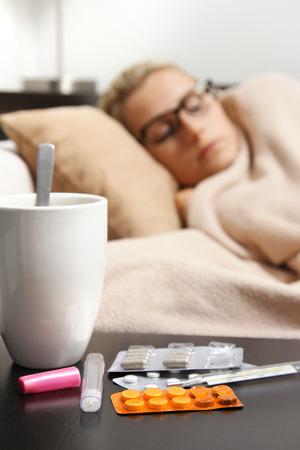 sick woman sleeping in bed, focus on pills