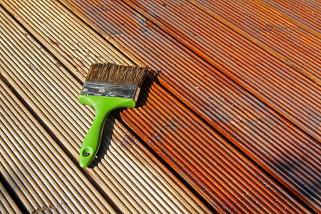 painting wooden patio deck with protective oil Stockfoto