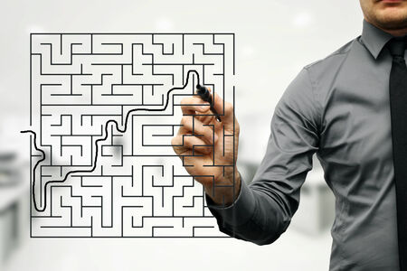conceptual image of businessman trying to find way out of maze photo