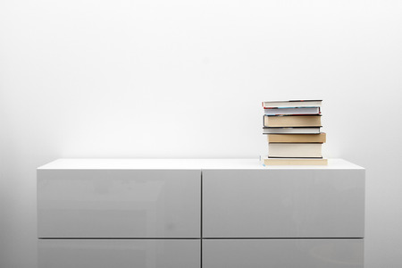 empty house: white commode with stack of books in bright minimalism interior