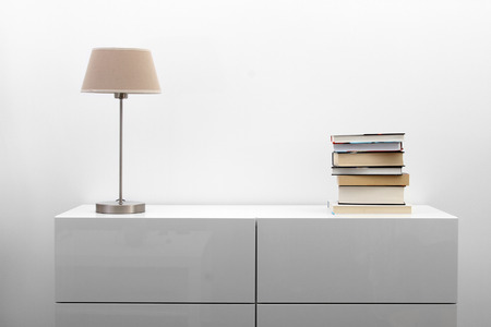wooden furniture: white commode with lamp and books in bright minimalism interior Stock Photo
