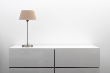 white commode with table lamp in bright minimalism interior Stockfoto