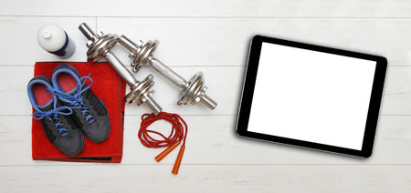 blank tablet: fitness equipment and blank digital tablet on gym floor Stock Photo