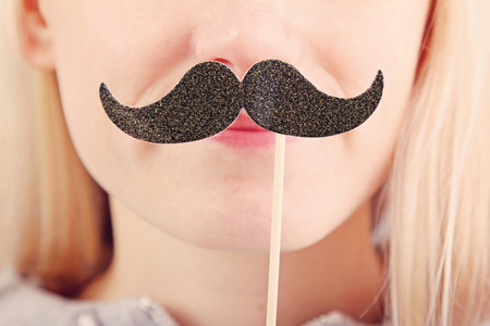 black head and moustache: woman holding mustache on a stick in front of her face