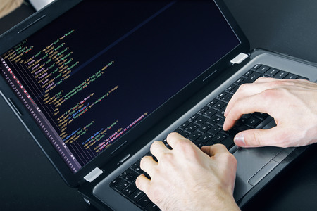 programmer occupation - writing programming code on laptop